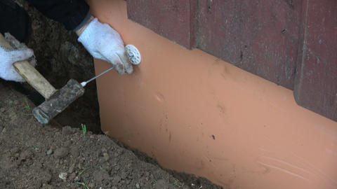 Worker with hammer and plastic anchor fixing polystyrene panel on foundation Footage