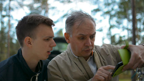 Father and son discussing a problem pointing at mobile phone and arguing outdoor Footage