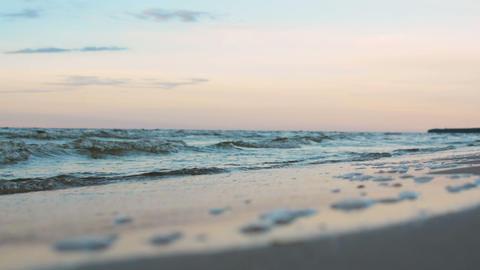 Small waves slowly rolling onto beach in twilight sunset blue evening light ビデオ