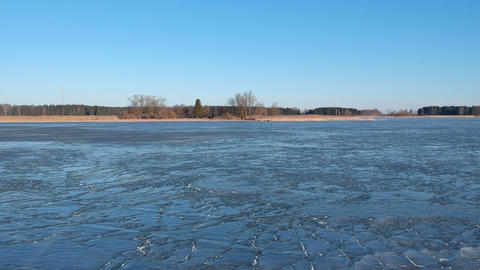 Drone fly above cracked spring lake ice, aerial Footage