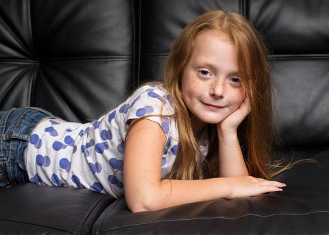 Little redhead girl with freckles resting on black sofa Fotografía