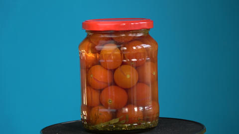 Rotating pickled glass jar with red tomato Footage