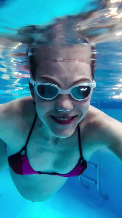Young pregnant woman swimming underwater in goggles Footage