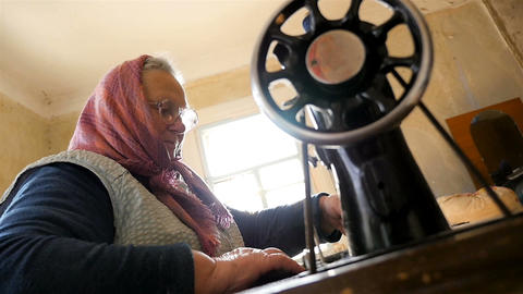Sewing clothes on a retro sewing machine. Elderly woman. Slow Motion Live Action