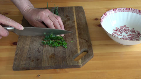 Cut fresh green onions on cutting board Live Action