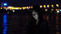 The girl uses a sartphone evenings against the background of the city having a Footage