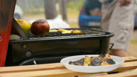 Burned potato chips and cooked apples closeup during family BBQ grill outside ビデオ