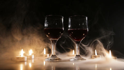 Wine glasses and burning candles in the smoke Footage