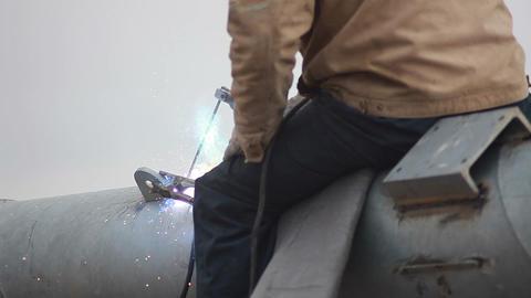 Welder welds fastening on a pipe Footage
