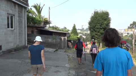 Group of pilgrims that go along on a paved road at the exit of the small village Footage