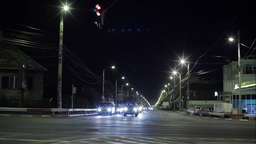 Heavy car traffic at an intersection illuminated by street lamps at night 78c Footage