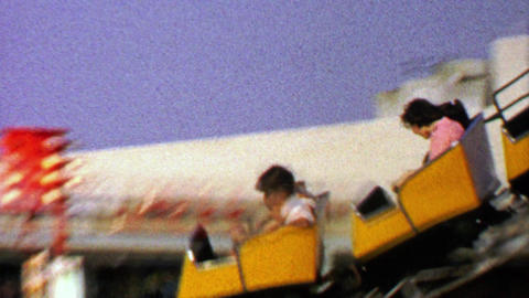 1967: Small carnival rollercoaster ride around festival parking lot Footage