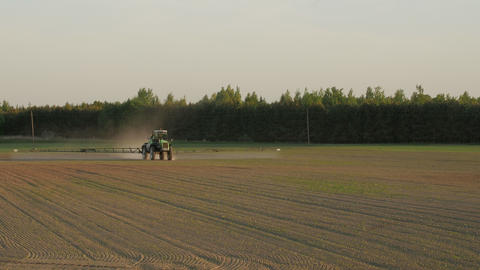 Tractor spray field with chemicals for crop plants protection from weed and pest GIF