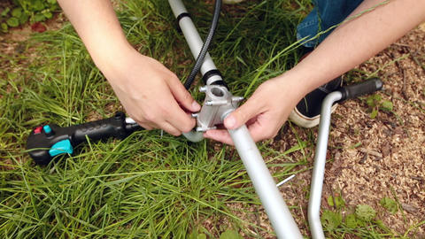A man assembling bush cutter or string trimmer in the garden Live Action