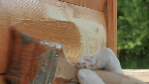 Closeup of hand in protective glove painting wooden plank house wall with GIF