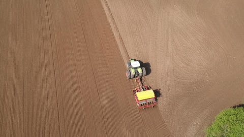 Agriculture tractor sowing crop on spring field, aerial ビデオ