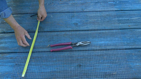 Measure and cut metal net on garden table Footage