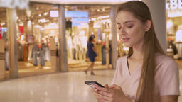 Young attractive girl goes shopping in mall, chattiong on smartphone, shopping Footage