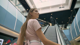 Young attractive girls standing on escalator in mall, holding bags, shopping Footage
