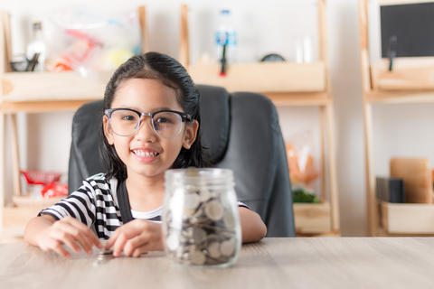 Asian little girl in smiling with the coin in a glass jar for sa フォト