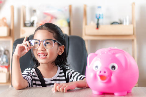 Asian little girl smiling with piggy bank shallow depth of field フォト