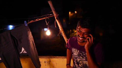 Handsome young man speaking and smiling on a mobile phone and smiling. Young man Live Action