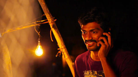 Casual young man talking on smart phone at night. Handsome young business man Live Action