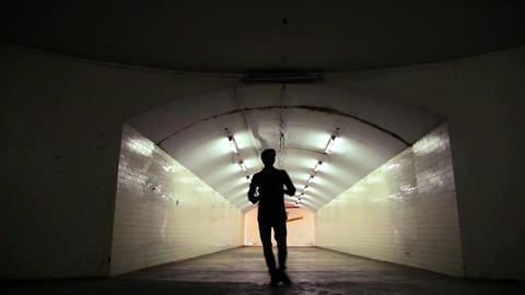 Silhouette man walking through an empty underground tunnel, single man alone Footage