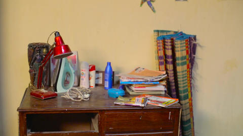 home interior, table with books, iron box and red lamp Live Action