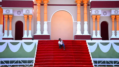 smiling young man speaking smartphone and sitting on red carpet steps, Colorful Footage