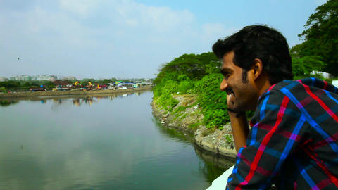 The man speaks of the smartphone, standing on the river's wall, panning shot Footage