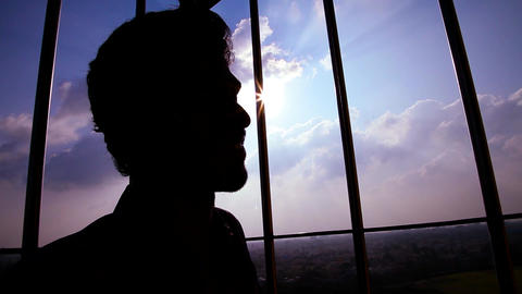 silhouette shot young man relaxes near a window, steams the sun, young man Live Action