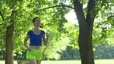 Smiling female runner running in summer park Footage