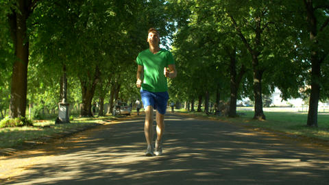 Athletic young man running in public park Footage