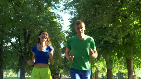 Active couple jogging together in summer park Footage