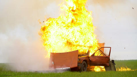 The car explosion in the field and burns out. The car is on fire Live Action