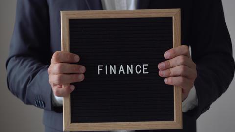 Word Finance from Letters on Text Board in Anonymous Businessman Hands Footage