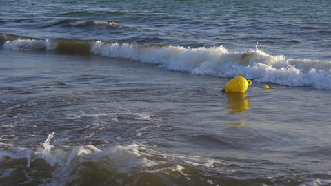 Yellow buoy floating in sea water slow motion. Sea buoy floating on water waves GIF