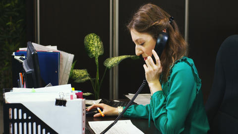 woman talks with clients on phone at workplace Footage