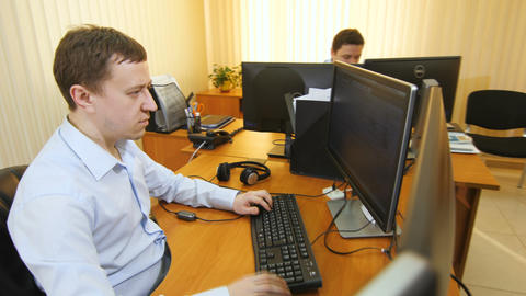 man types on keyboard sitting near colleague working on computer Footage