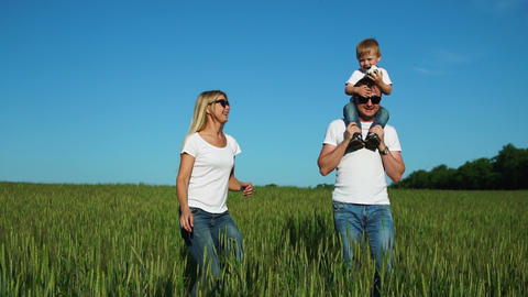 Walking family in the field with one child in white t-shirts Live Action