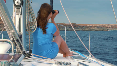 Womanin a blue dress sits aboard the yacht and exploring the horizon through Footage