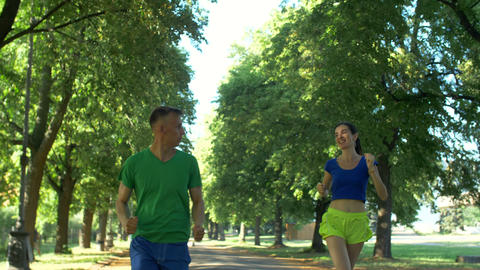 Cheerful female runner overtake man on park trail Footage