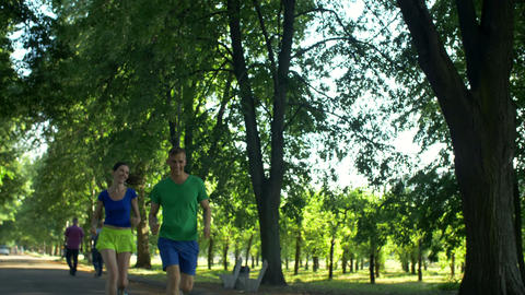 Positive male athlete outrunning female jogger Footage