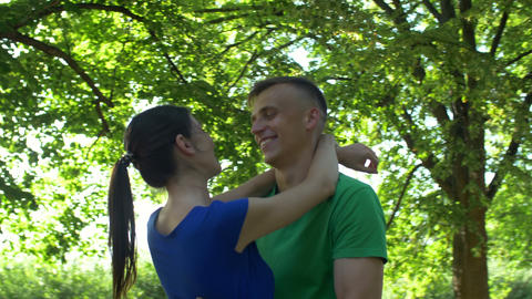 Happy couple in love embracing in public park Footage