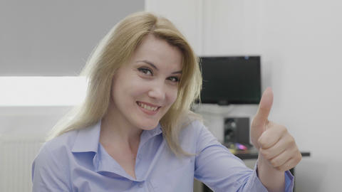 Successful beautiful young entrepreneur woman at home office pointing thumbs up Footage