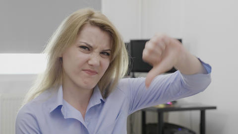 Disgusted young businesswoman showing thumbs down sign of dislike Live Action