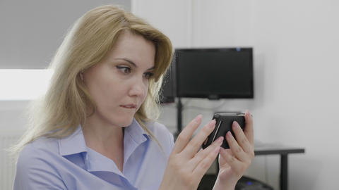 Shocked young businesswoman receiving surprising breaking news on her smartphone Live Action