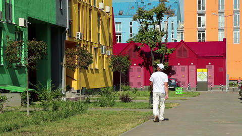Man in white clothes walks down the street with manycoloured buildings Footage