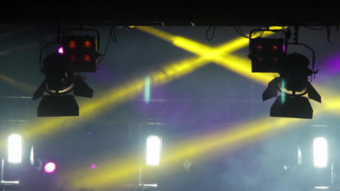 Multicolored spotlights mounted above the stage in whose light shows the dust ra Footage